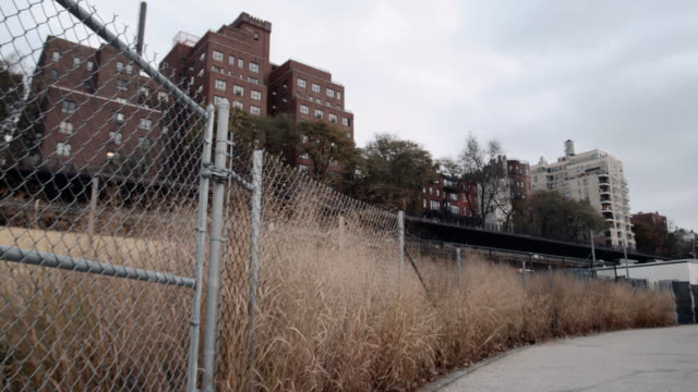 A gritty exterior shot of a fence and traffic passing in front of an unrecognizable apartment building in Brooklyn
