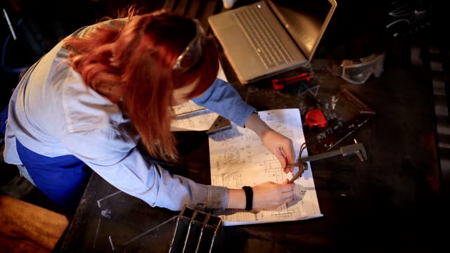 gritty young mechanic woman working hard in workshop - drawing compass stock videos & royalty-free footage