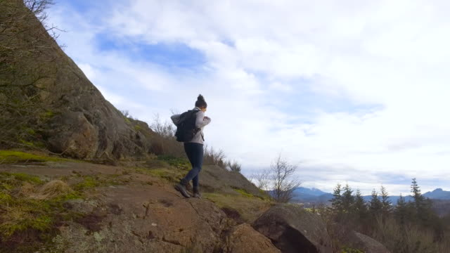 Gritty young woman hiking solo