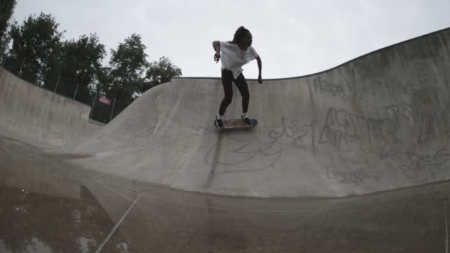 a gritty, young woman shreds the pool at a local skatepark - 4k - slow motion - wide shot stock videos & royalty-free footage