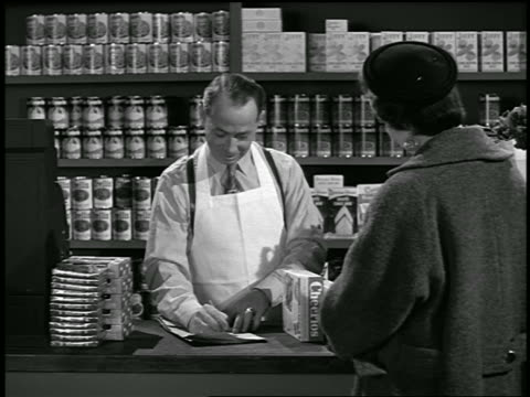 b/w 1954 grocer adding up purchases of woman in grocery store / industrial - 1954 stock videos & royalty-free footage