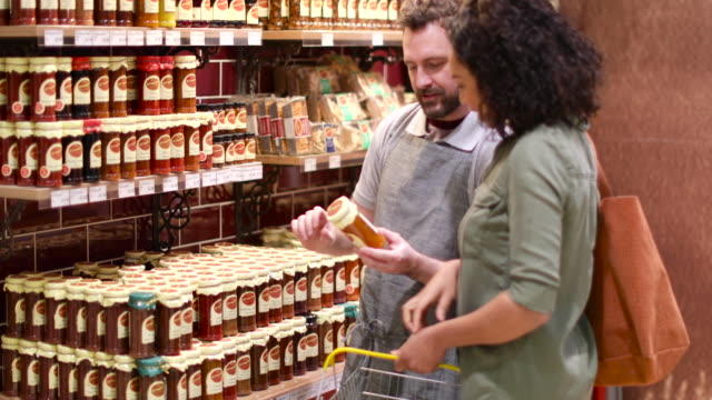 vidéos et rushes de grocer advising customer in store on ingredients - vendeur