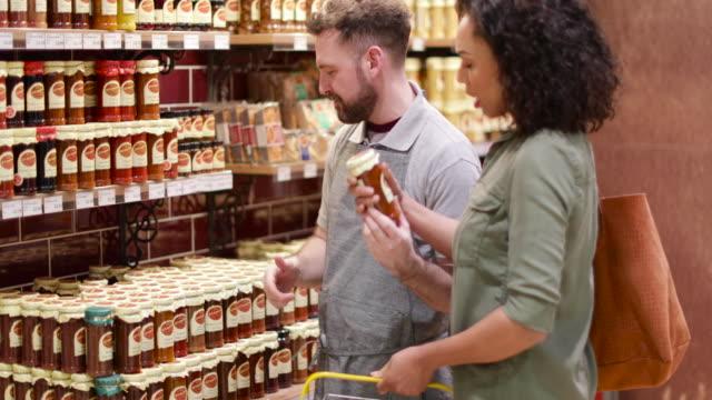 vidéos et rushes de grocer advising customer in store - vendeur
