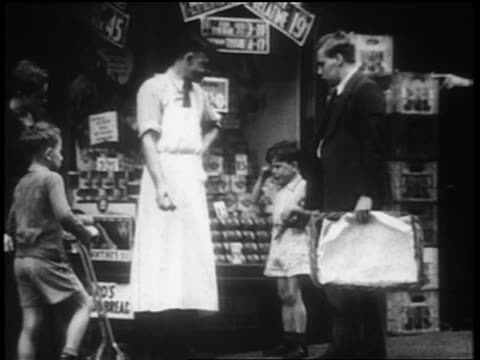 B/W 1939 grocer talking to crying boy + father in front of store on sidewalk / NYC / documentary
