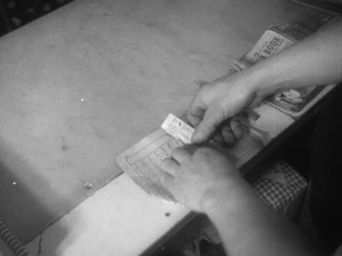 a grocer tears our ration points from a ration book - food stamps stock videos & royalty-free footage