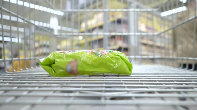 vídeos de stock, filmes e b-roll de carrinho de supermercado se move ao redor do supermercado com comida. - mercado espaço de venda no varejo