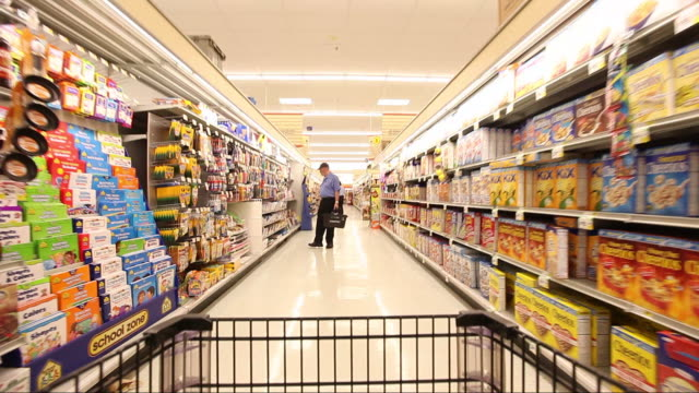 vidéos et rushes de grocery cart pov rolls down a food aisle past other shoppers. - supermarché