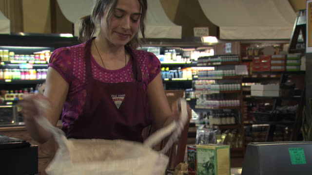 grocery clerk bagging groceries in a reusable bag - see other clips from this shoot 1172 stock videos & royalty-free footage