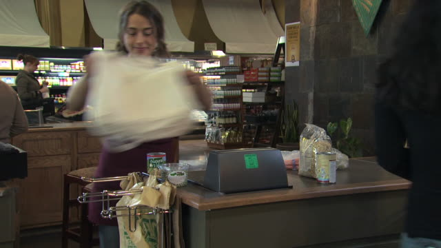 vidéos et rushes de grocery clerk bagging groceries in a reusable bag - sac de shopping