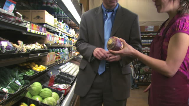 grocery clerk helping a man with organic produce - see other clips from this shoot 1172 stock videos & royalty-free footage