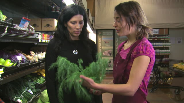 grocery clerk helping a woman with organic produce - see other clips from this shoot 1172 stock videos & royalty-free footage