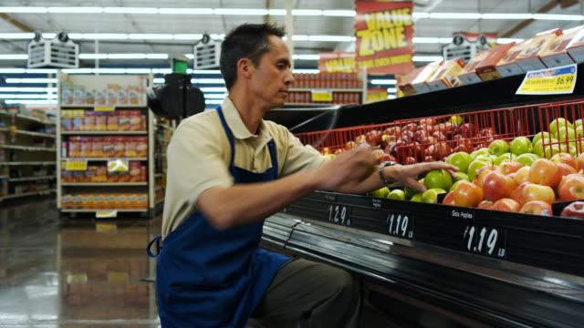 grocery clerk putting apples away - grocer stock videos & royalty-free footage