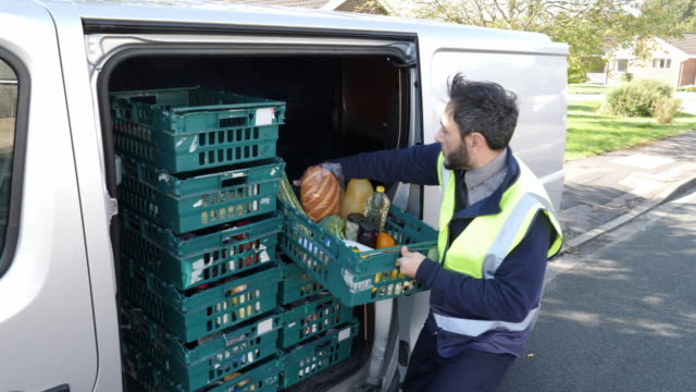 vídeos de stock e filmes b-roll de 4k: grocery delivery driver from supermarket lifts crate of food out of the van - carrinha veículo