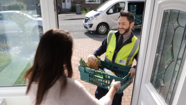 4K: Grocery delivery man from Supermarket delivers online shopping food order to front door of home