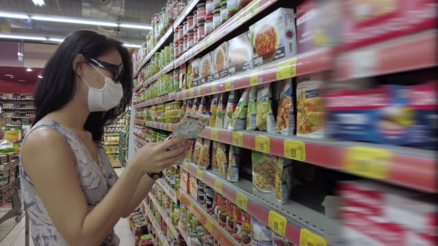 grocery shopping at supermarket with surgical mask - canned food stock videos & royalty-free footage