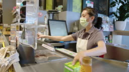 Grocery store worker doing checkout for customer