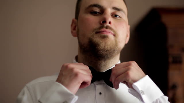 CLOSE UP Groom adjusting black bowtie