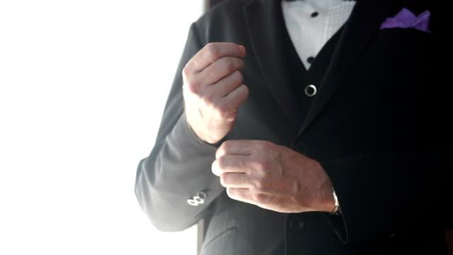 groom adjusting his cufflinks suit on white background. - cufflink stock videos & royalty-free footage