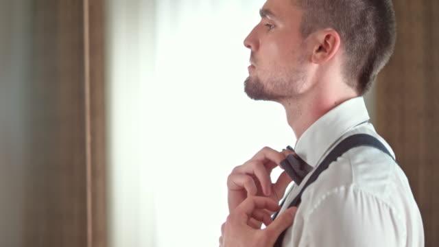 TU bruidegom zijn bretels en een strikje aan te passen