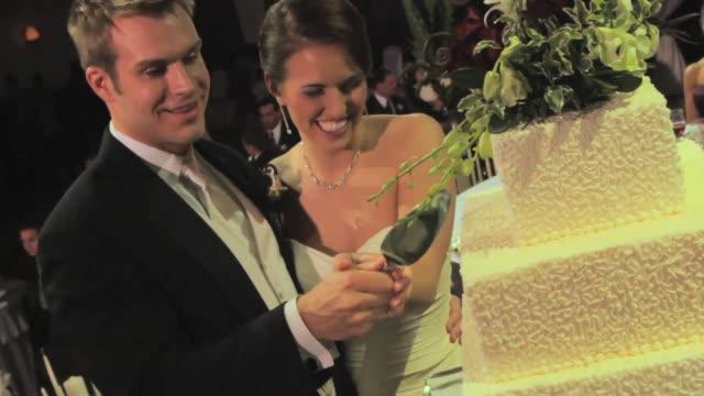 vidéos et rushes de groom and bride cut cake together - le marié