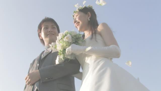 groom and bride standing arm in arm under shower flowers - 向かい合わせ点の映像素材/bロール