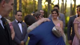 Groom being congratulated by his mother in law at wedding ceremony