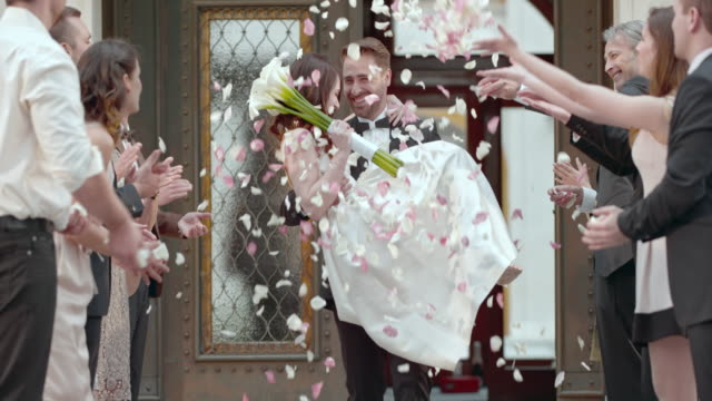 slo mo groom carrying bride from church in flower shower - portare video stock e b–roll