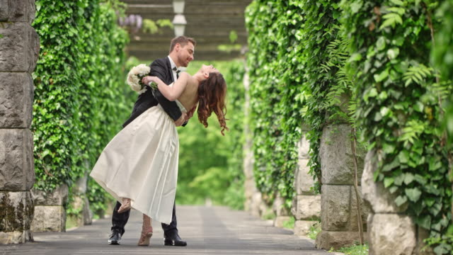 slo mo groom dancing with his bride in the passageway - bridegroom stock videos and b-roll footage
