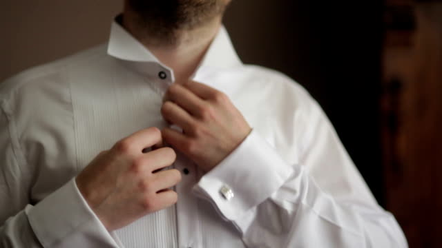 CLOSE UP Groom fastening white shirt