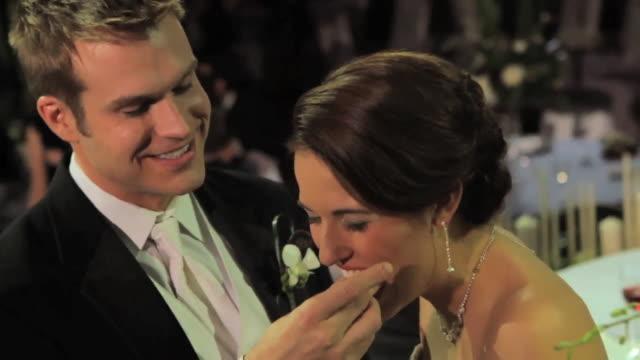Groom feeds wedding cake to bride