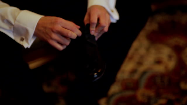 CLOSE UP PANNING Groom holding black shoe