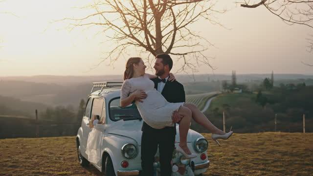 丘の上で腕に花嫁を抱いた新郎 - 白のドレス点の映像素材/bロール