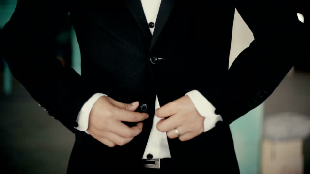 Groom in black suit with buttoning his jacket.