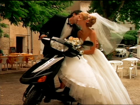 A groom kisses his bride as she sits on a motor scooter.