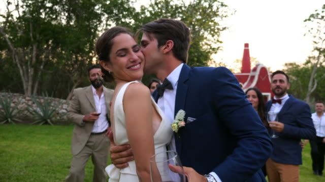MS Groom kissing bride on cheek during wedding reception at tropical resort