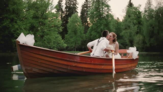 SLO MO Groom kissing the bride on the lake