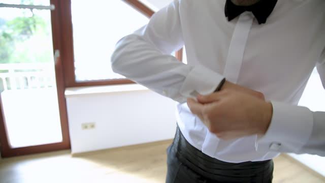 groom preparing for wedding day. man adjusting his cufflinks on white shirt - cufflink stock videos & royalty-free footage
