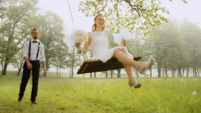 SLO MO Groom pushing his bride on a swing in sunshine