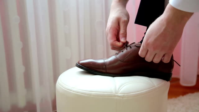 Groom tying his shoes