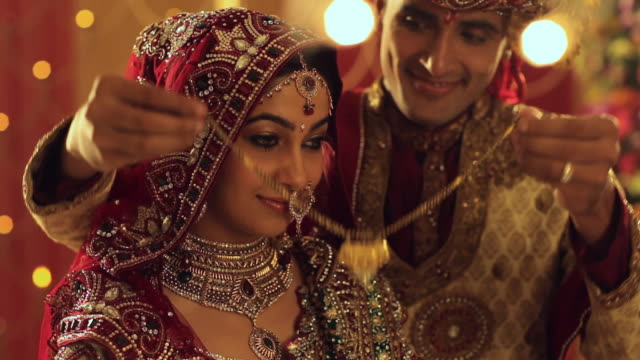 vidéos et rushes de groom wearing necklace to his wife  - indien d'inde