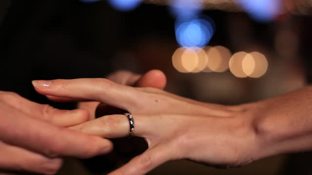 handheld close up groom's hand puts wedding ring on bride's finger as camera flashes go off - married stock videos & royalty-free footage
