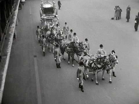 groomsmen and coachmen lead the royal grey horses around the royal mews as they pull the gold state coach in preparation for the coronation of... - gold colored点の映像素材/bロール