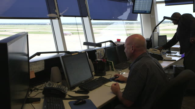 Ground control operations tower interior with airplane visible in background/DFW International Airport, Dallas-Fort Worth, Texas, USA