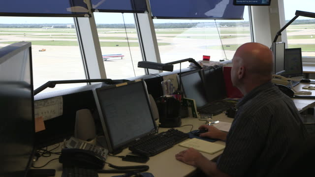 vídeos de stock, filmes e b-roll de ground control operations tower interior with airplane visible in background/dfw international airport, dallas-fort worth, texas, usa - torre de controle de tráfego aéreo