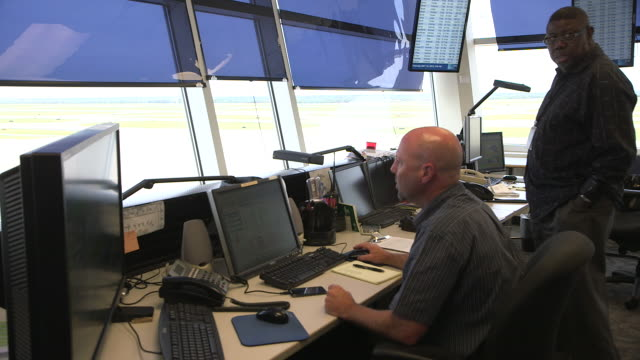 Ground control workers direct airplane traffic inside control tower/DFW International Airport, Dallas-Fort Worth, Texas, USA