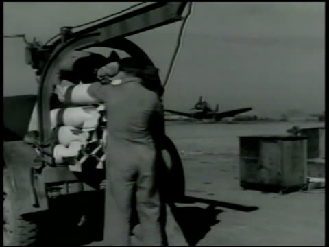 Ground crew loading bomb shell onto back of truck MS Naval Air Force pilot climbing into cockpit of fighter airplane WS Two airplanes taking off on...