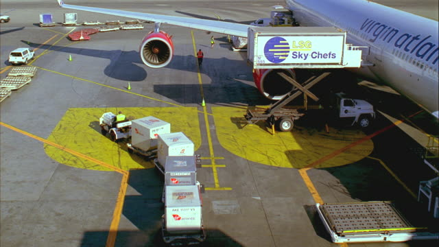 t/l, ha, ms, ground crew loading commercial aircraft on tarmac, los angeles, california, usa - エプロン点の映像素材/bロール