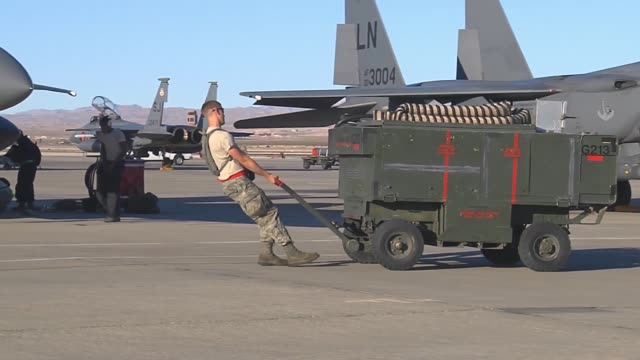 a ground crew member pulls a cart of equipment across the flightline during red flag 143 jul 21 2014 at nellis air force base nev red flag gives... - nellis air force base stock videos and b-roll footage