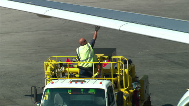 ms, zo, ha, ground crew member refueling commercial jet on tarmac, los angeles, california, usa - tanken stock-videos und b-roll-filmmaterial