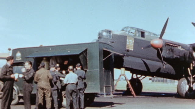 raf ground crew of parked lancaster heavy bomber gathering around snack truck waaf climbing from back of truck and serving coffee and pastries to... - lancaster bomber stock videos & royalty-free footage